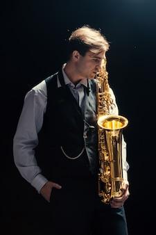 Junger mann, der das saxophon spielt