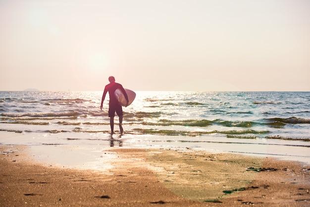 Junger mann, der das surfbrett läuft auf die küste hält