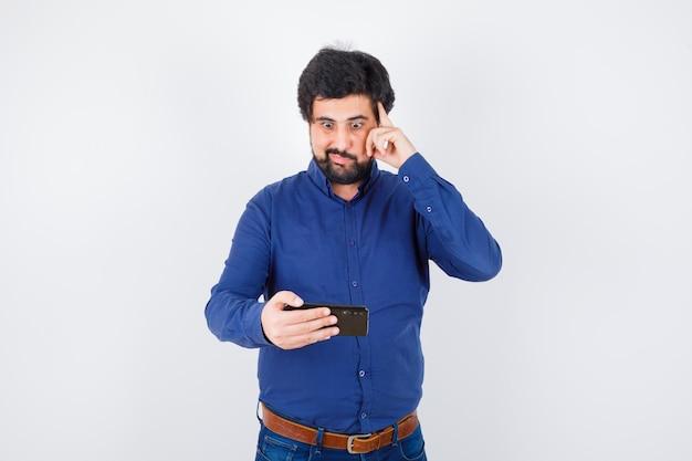 Junger mann, der das telefon mit der hand auf dem kopf im königsblauen hemd betrachtet und froh schaut. vorderansicht.