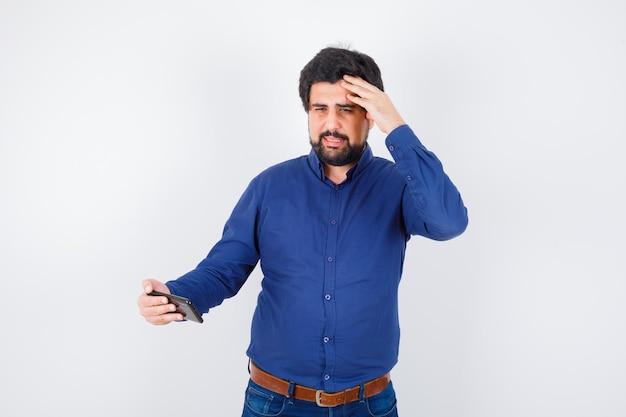 Junger mann, der das telefon mit der hand auf dem kopf im königsblauen hemd betrachtet und verängstigt aussieht, vorderansicht.