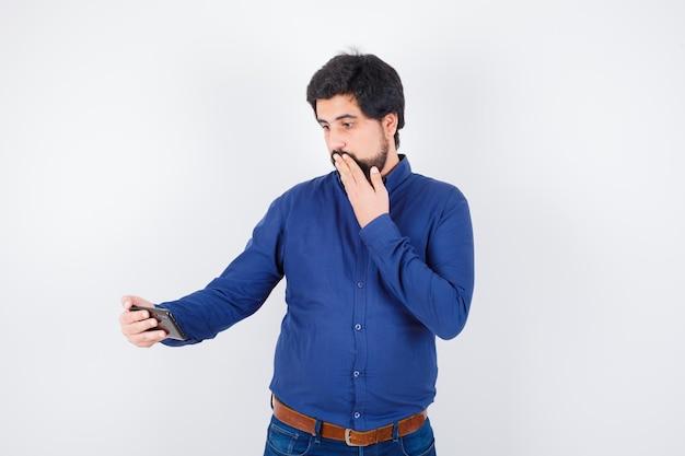 Junger mann, der das telefon mit der hand auf dem mund im königsblauen hemd betrachtet und verängstigt aussieht, vorderansicht.