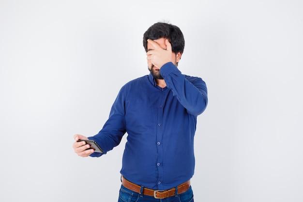 Junger mann, der das telefon mit der hand auf den augen im königsblauen hemd betrachtet und verängstigt aussieht, vorderansicht.