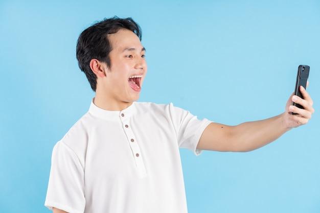 Junger mann, der das telefon mit einem glücklichen ausdruck hält