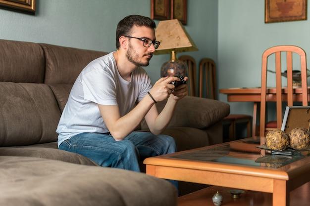 Junger mann, der das videospiel hält drahtlosen prüfer spielt