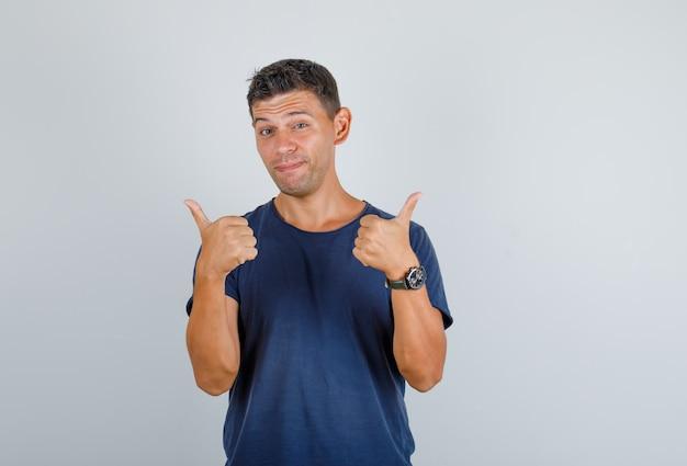 Junger mann, der daumen hoch im dunkelblauen t-shirt zeigt und froh aussieht. vorderansicht.