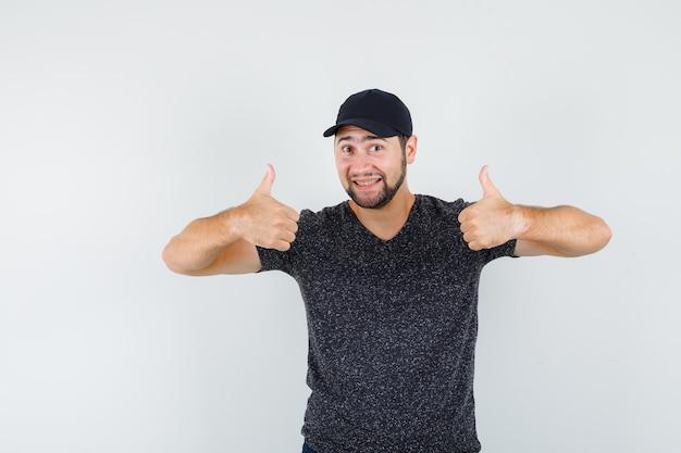 Junger mann, der daumen hoch in t-shirt und mütze zeigt und fröhlich aussieht