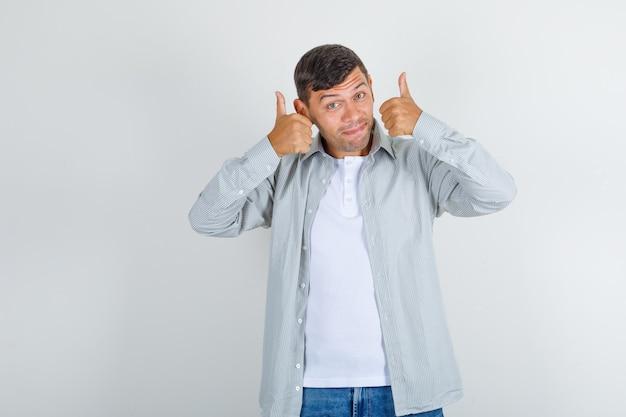 Junger mann, der daumen in hemd, jeans zeigt und froh aussieht