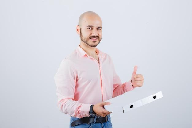 Junger mann, der daumen in hemd, jeans zeigt und selbstbewusst aussieht, vorderansicht.