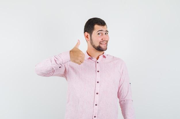 Junger mann, der daumen oben im rosa hemd zeigt und froh schaut