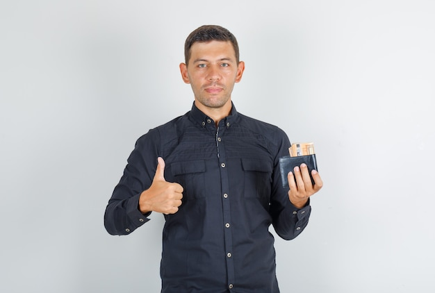 Junger mann, der daumen oben mit brieftasche im schwarzen hemd zeigt und glücklich schaut