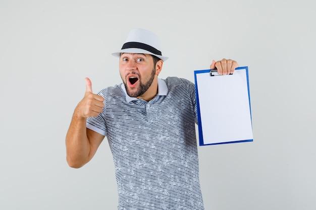 Junger mann, der daumen oben zeigt, während er sein notizbuch im t-shirt, im hut hält und amüsiert, vorderansicht schaut.