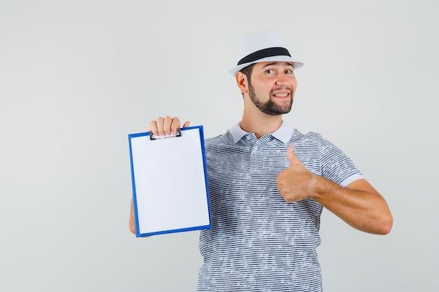 Junger mann, der daumen oben zeigt, während er sein notizbuch im t-shirt, im hut hält und zuversichtlich schaut, vorderansicht.