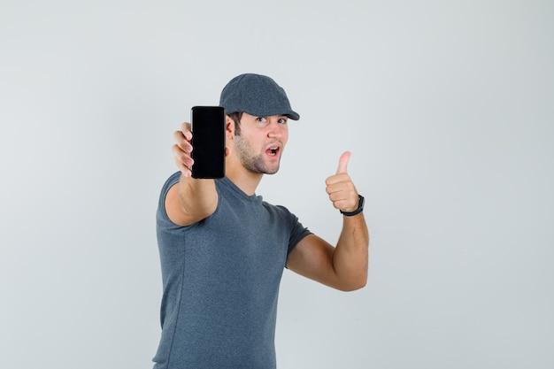 Junger mann, der daumen oben zeigt, während handy in der t-shirt-kappe hält