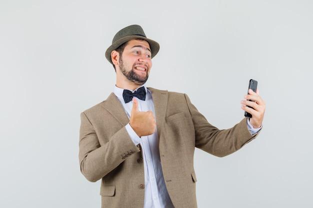 Junger mann, der daumen oben zeigt, während selfie in anzug, hut und fröhlich aussehend, vorderansicht nimmt.