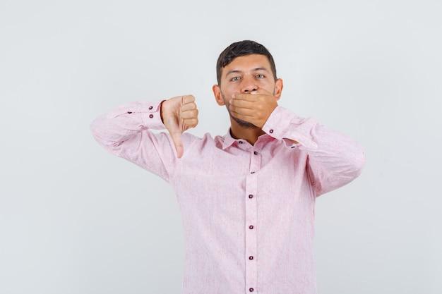 Junger mann, der daumen unten mit hand auf mund in der rosa vorderansicht des hemdes zeigt.