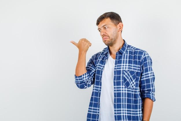 Junger mann, der daumen weg im hemd zeigt und verwirrt schaut. vorderansicht.