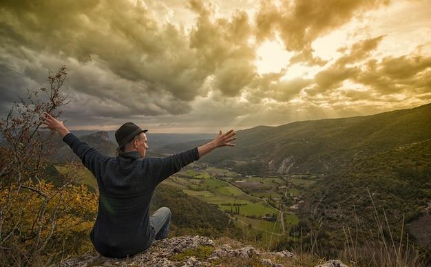 Junger mann, der den berg sonnenuntergang betrachtet