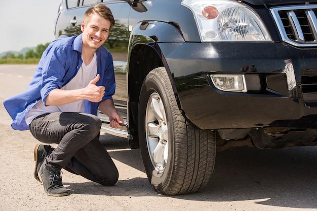Junger mann, der den durchbohrten reifen auf seinem auto ändert.