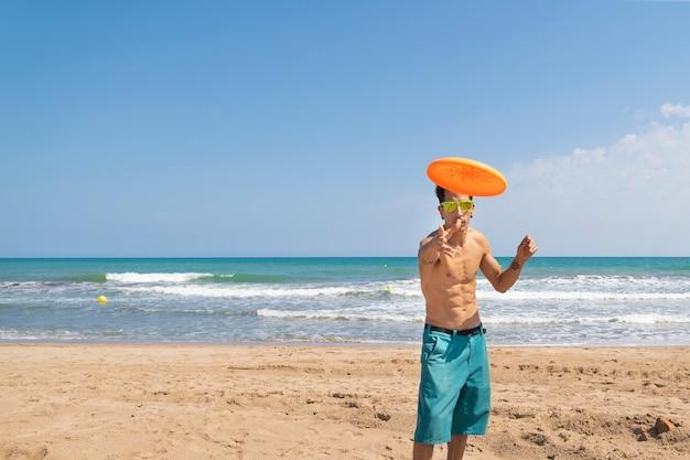 Junger mann, der den frisbee im strand spielt