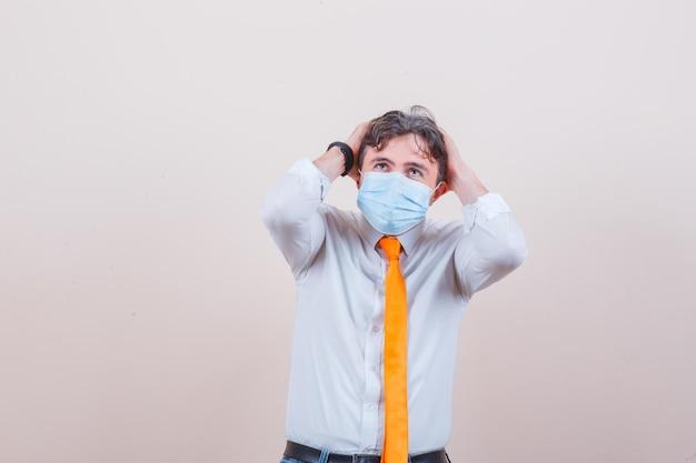 Junger mann, der den kopf in hemd, krawatte, maske in die hände hält und verängstigt aussieht