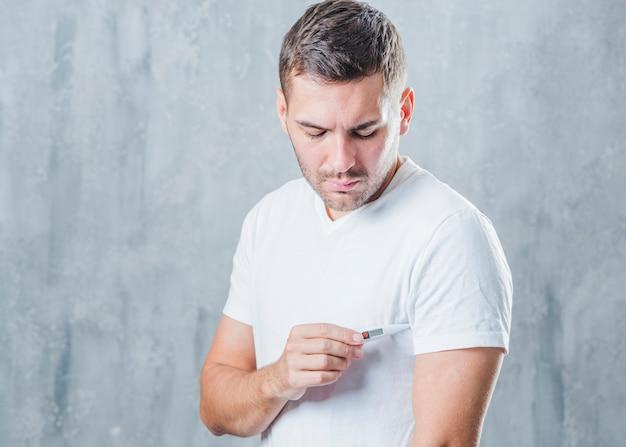 Junger mann, der den medizinischen digitalen thermometer in seinen unter achselhöhle einsetzt