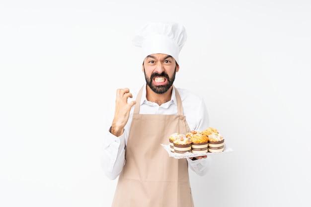 Junger mann, der den muffinkuchen frustriert durch eine schlechte situation hält