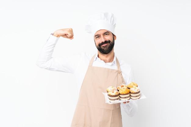 Junger mann, der den muffinkuchen tut starke geste hält