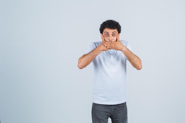 Junger mann, der den mund mit den händen in weißem t-shirt und jeans bedeckt und überrascht aussieht. vorderansicht.