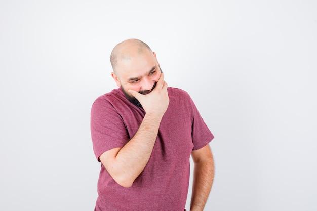 Junger mann, der den mund mit der hand bedeckt, während er die hand in rosa t-shirt an der taille hält und nachdenklich aussieht, vorderansicht.
