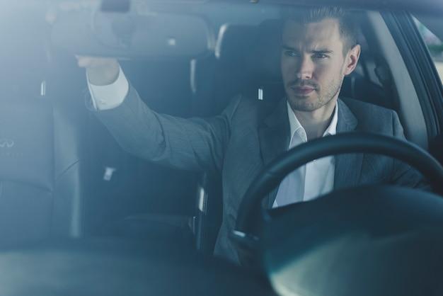 Junger mann, der den rückspiegel im auto justiert