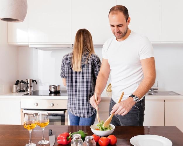 Junger mann, der den salat und ihre frau zubereiten, die hinter ihm kochen lebensmittel in der küche stehen