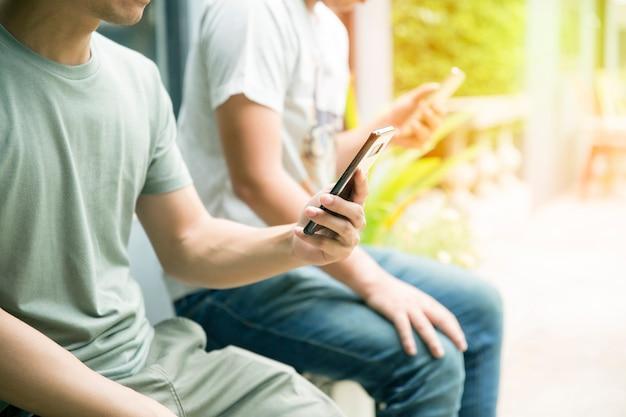 Junger mann, der den smartphone plaudert mit ihrem handy-suchen oder konzept der sozialen netzwerke verwendet