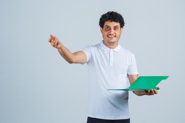 Junger mann, der den stift in der heureka-geste anhebt und ein notizbuch in weißem t-shirt und jeans hält und glücklich aussieht. vorderansicht.