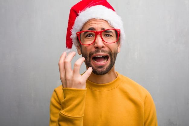 Junger mann, der den weihnachtstag hält, der geschenke sehr erschrocken und ängstlich hält