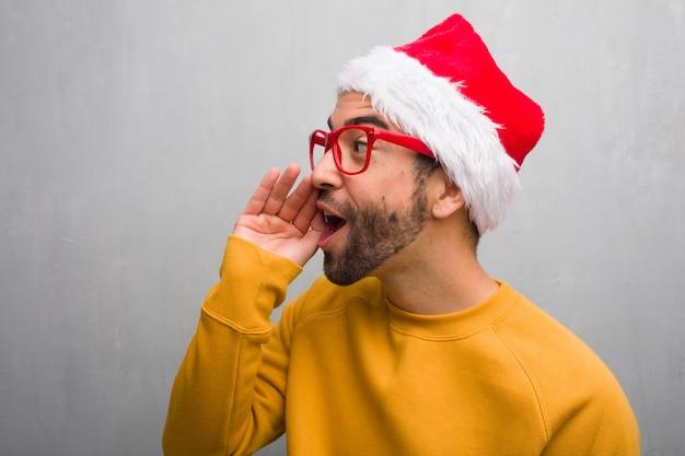 Junger mann, der den weihnachtstag hält die geschenke hält, die klatschuntergehen flüstern