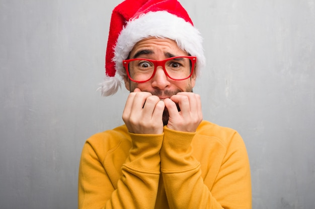 Junger mann, der den weihnachtstag hält geschenke beißend nägeln, nervös und sehr besorgt feiert
