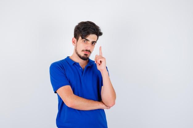 Junger mann, der den zeigefinger in der heureka-geste im blauen t-shirt hebt und ernst schaut