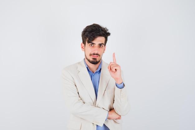 Junger mann, der den zeigefinger in der heureka-geste in blauem t-shirt und weißer anzugjacke hebt und ernst aussieht