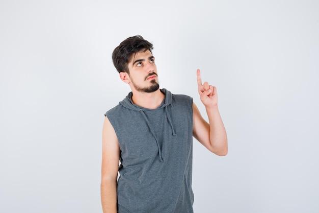 Junger mann, der den zeigefinger in der heureka-geste in grauem t-shirt hebt und ernst aussieht