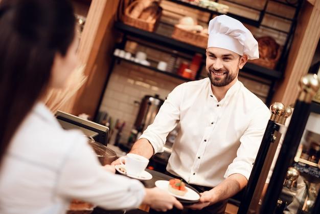 Junger mann, der der frau in der bäckerei kuchen und tee verkauft