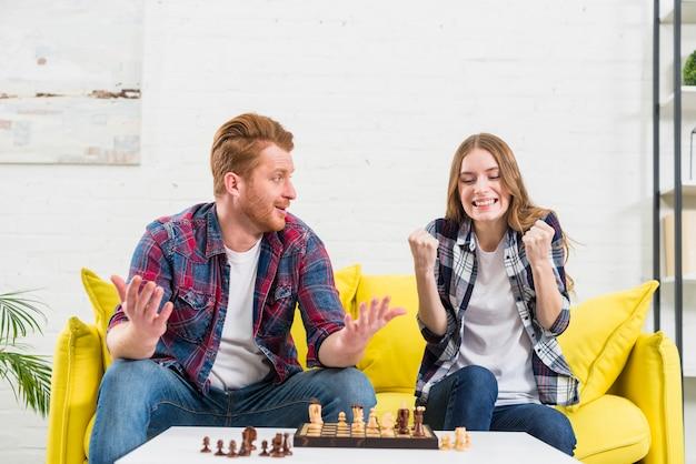Junger mann, der der freundin, die ihre faust mit erfolg zusammenpreßt, nach dem gewinnen des schachspiels zuckt und betrachtet