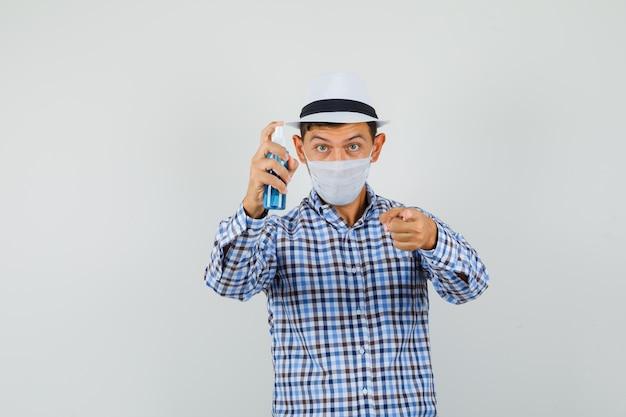 Junger mann, der desinfektionsspray hält und auf kamera im karierten hemd zeigt