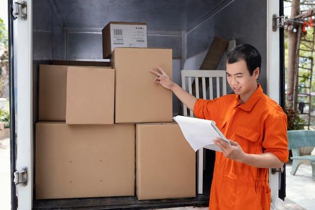 Junger mann, der details der pakete vor der lieferung prüft