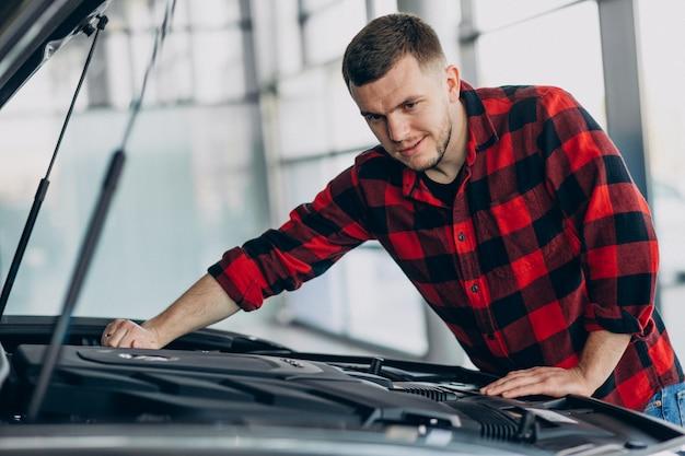 Junger mann, der diagnose des fahrzeugs macht