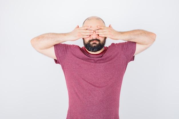 Junger mann, der die augen mit den händen im rosa t-shirt bedeckt und ernst schaut. vorderansicht.