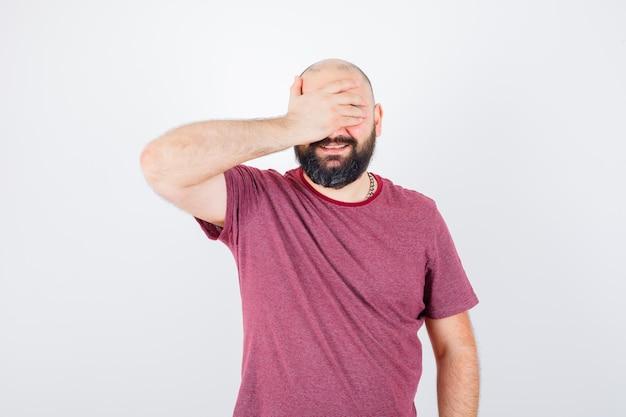 Junger mann, der die augen mit der hand bedeckt, während er in rosa t-shirt lacht und optimistisch aussieht, vorderansicht.