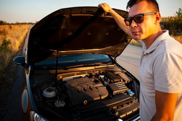 Junger mann, der die autohaube öffnet