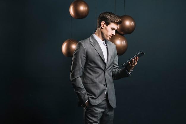 Junger mann, der die digitale tablette steht vor rundem kupfernem leuchter des stromlinienförmigen spiegels betrachtet