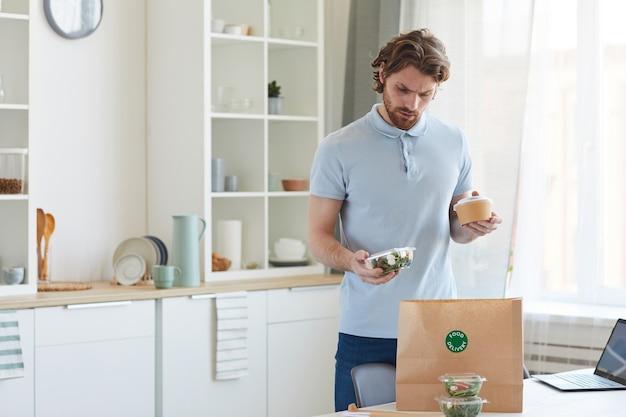 Junger mann, der die essenslieferung erhält, packt die papiertüte mit essen aus, während er in der küche steht