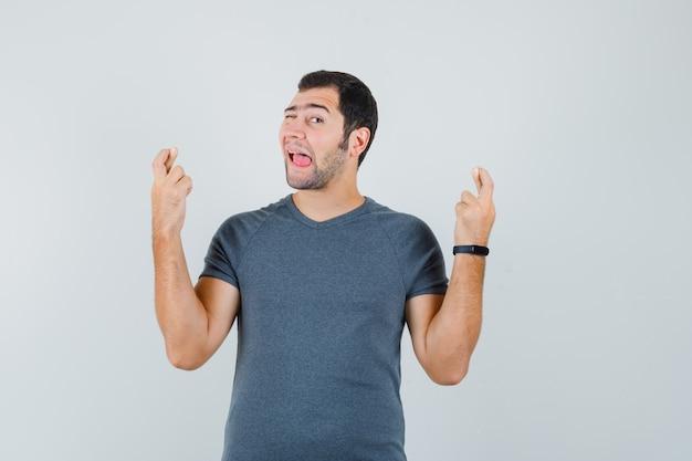 Junger mann, der die finger gekreuzt hält, zwinkert auge, das zunge in grauem t-shirt herausragt